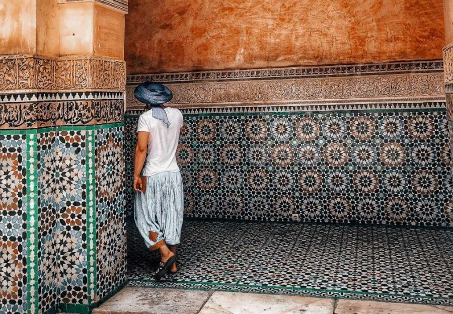 Man in Morocco with back facing the camera, walking in front of beautiful Moroccan tile